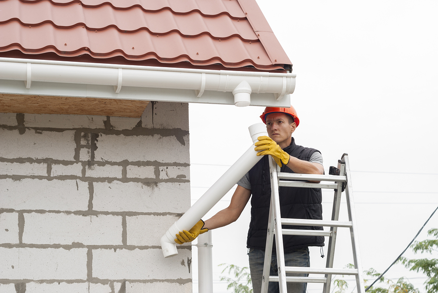 professional roofer doing gutter installation