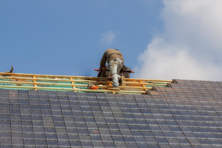 this image shows a roofer doing a metal roofing for tracy roofing pros