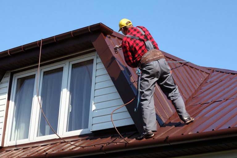 this image shows tracy types of roofs with a roofer performing roof repair