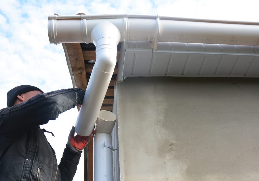 professional roofer doing gutter installation